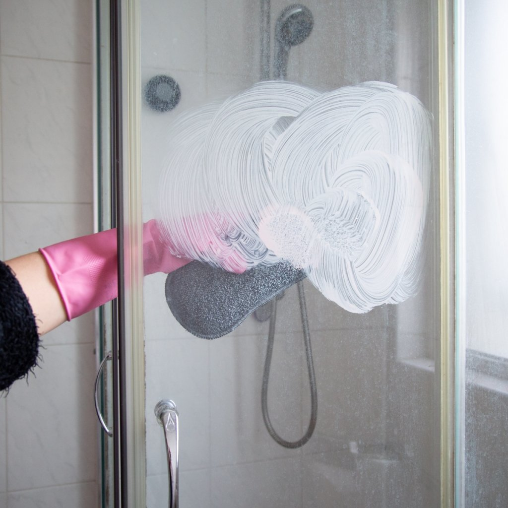 shower door with person using the pink stuff paste
