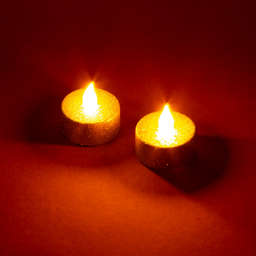 two gold glitter tealights with fake flame